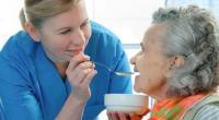 Медсестра помогает больной есть